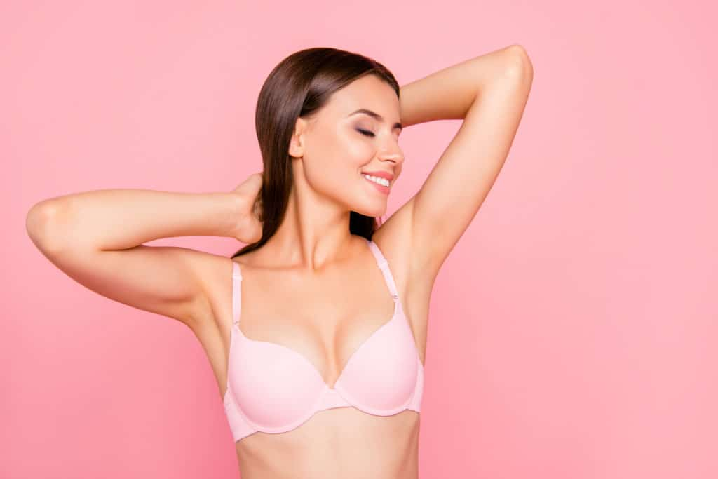 Young smiling woman wearing a pink bra